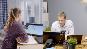 split screen shows students at laptop on lieft, teacher at right, both looking at computers