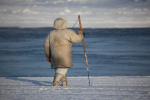 man with harpoon walking on open ice