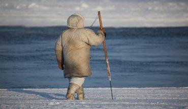 man with harpoon walking on open ice