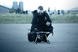 man wearing mask checks small drone on tarmac