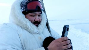 Inuit man using smartphone app outdoors
