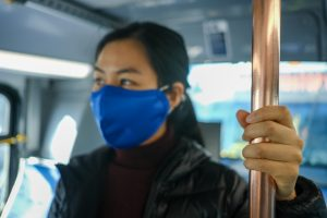 woman wearing mask holds post while riding bus