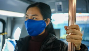 woman wearig mask holds post while riding bus