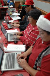 people seated at computers, all wearing Santa hats