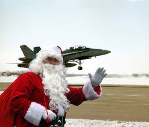 Santa Clas waves as a fighter jet takes off behind him