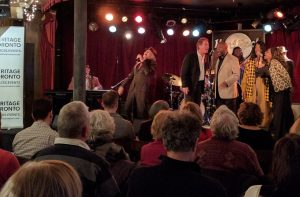 musicians perform on stage as seated crowd looks on