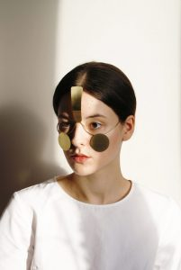 woman wears unusual face jewellery with metal circles under her eyes and a bar across her foreheasd