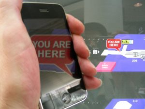 hand holds smartphone with you are here on screen