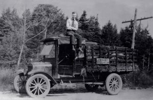 old photo shows grocer's truck with man sitting on roof