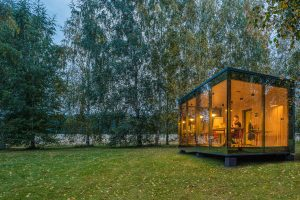 large glass booth is seen in outdoor natural setting