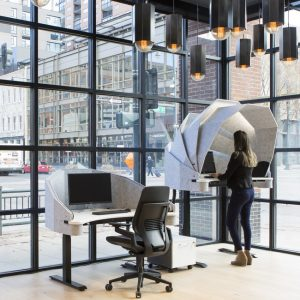 woman stands at desk with dome like structure