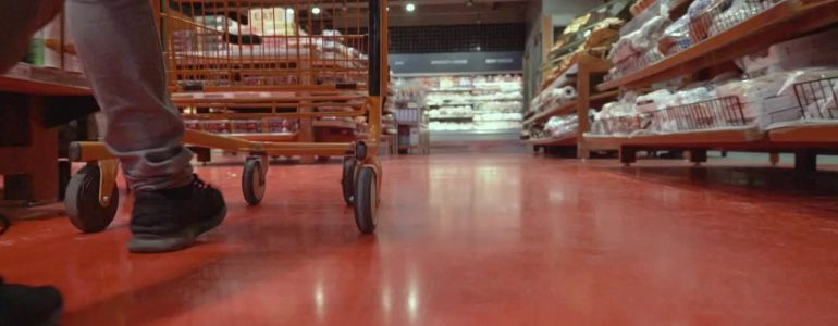 man pushes grocery cart down aisle