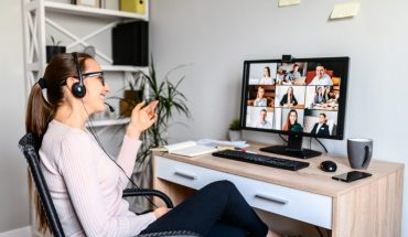 woman in videoconference call sits at home base computer work station