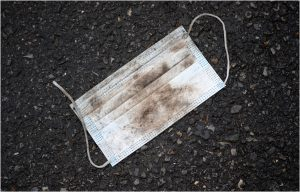 dirty used face masks on the ground