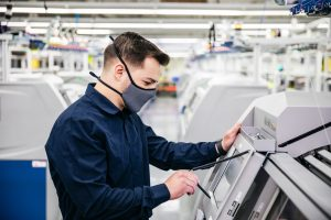 man wearing mask looks at industrial machine