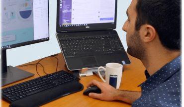 man at computer desk, two screens visible