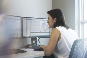 woman sits at copmuter conole with multiple screens