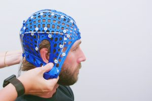 man is fitted with skill cap embedded with sensors and wires