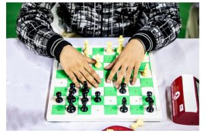 hands rest on a touch sensitive chess board