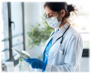 doctor wearing mask and gown looks at tablet computer