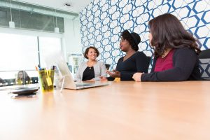 women seated at table in tech office